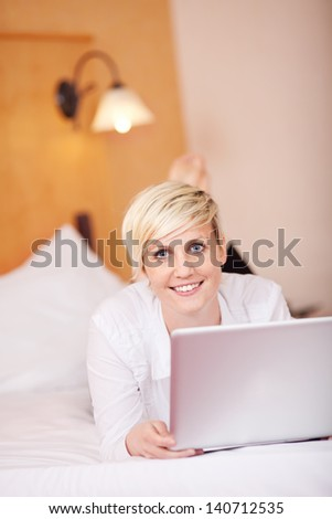 Portrait of smiling businesswoman with laptop while lying on bed in hotel room - stock photo