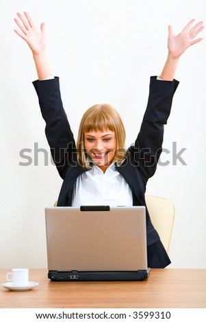 Portrait of smiling businesswoman with raised hands sitting at the table with the opened laptop and a cup on it - stock photo