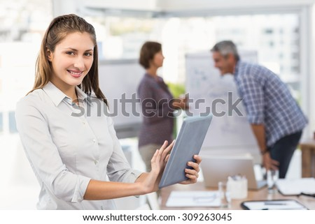 Portrait of smiling businesswoman with tablet in a meeting in the office