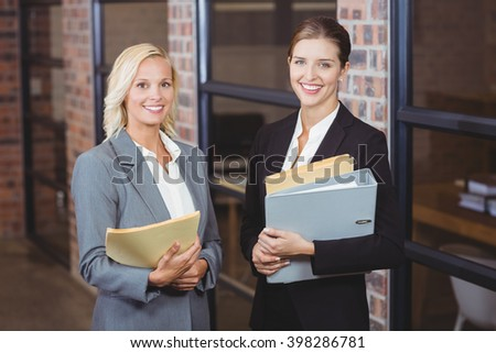 Portrait of smiling businesswomen holding documents while discussing at office - stock photo