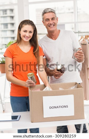 Portrait of smiling casual business colleagues sorting donations in the office - stock photo