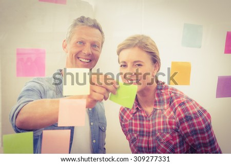 Portrait of smiling casual businessman showing sticky note to colleague in the office - stock photo