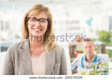 Portrait of smiling casual businesswoman in front of her colleague in the office - stock photo