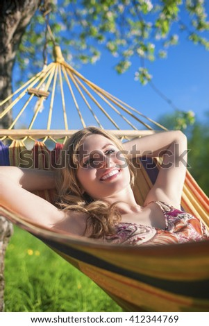 Portrait of Smiling Caucasian Blond Lady Resting in Hummock During Spring Time Outdoors.Vertical Shot - stock photo
