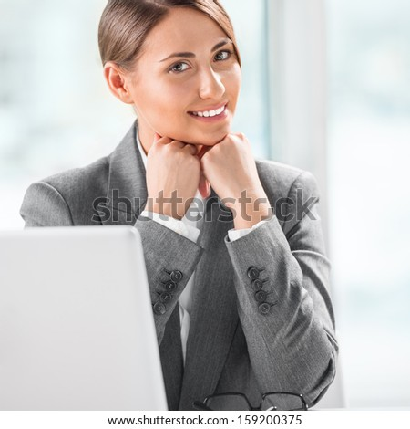 Portrait of smiling caucasian female executive working on laptop and making pause