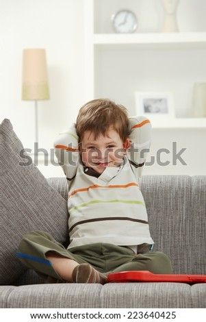 Portrait of smiling caucasian kid sitting on sofa at indoor home. Looking at camera. - stock photo