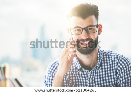 Portrait of smiling caucasian male talking on mobile phone