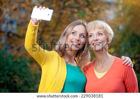 Portrait of smiling caucasian middle aged mother and her blonde adult daughter doing selfie by white mobile phone outdoor - stock photo