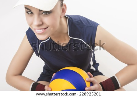 Portrait of Smiling Caucasian Professional Female Volleyball Player Equipped in Volleyball Outfit and Wearing Vizor and Holding Ball. Over White Background. Horizontal Shot - stock photo