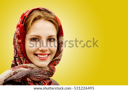 Portrait of smiling charming young woman in headscarf isolated on yellow background.