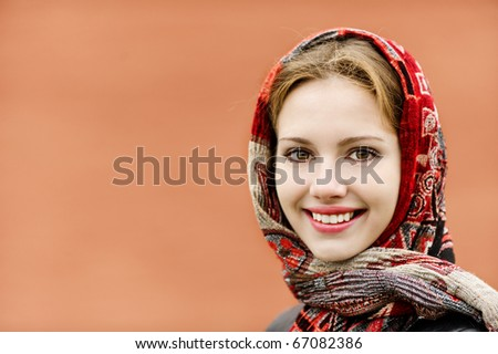 Portrait of smiling charming young woman in headscarf on red background. - stock photo