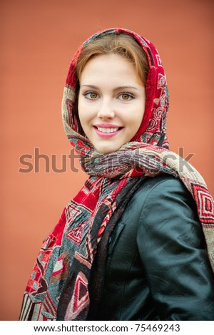 Portrait of smiling charming young woman in headscarf on red background - stock photo