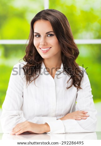 Portrait of smiling cheerful brunette businesswoman at office - stock photo