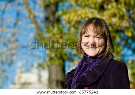 portrait of smiling cheerful laughing student girl outdoors in autumn - stock photo