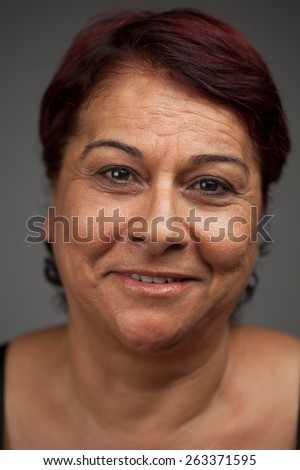 Portrait of smiling cheerful middle-aged woman isolated on gray