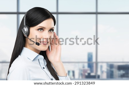 Portrait of smiling cheerful support phone operator in headset. New York panoramic office background. - stock photo