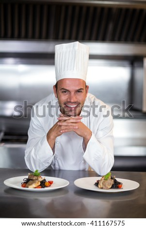 Portrait of smiling chef standing in commercial kitchen - stock photo