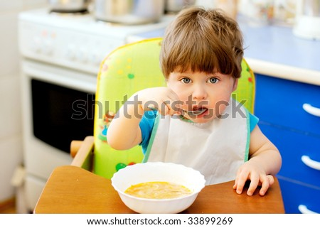 portrait of smiling child in the kitchen - stock photo