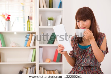 Portrait of smiling chinese woman using laptop with livingroom background drinking coffee