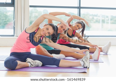 Portrait of smiling class and instructor doing stretching pilate exercises in fitness studio - stock photo