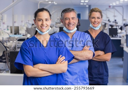 Portrait of smiling co-workers in a line with arms crossed in dental clinic - stock photo