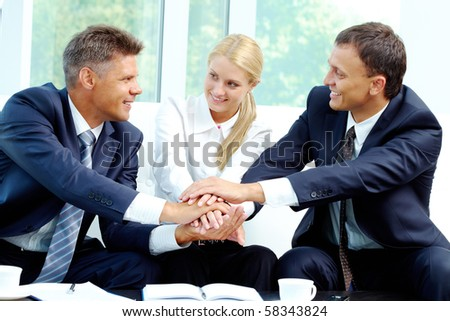 Portrait of smiling co-workers making pile of hands and looking at each other - stock photo