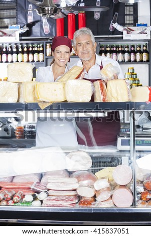 Portrait Of Smiling Colleagues Selling Cheese In Store - stock photo