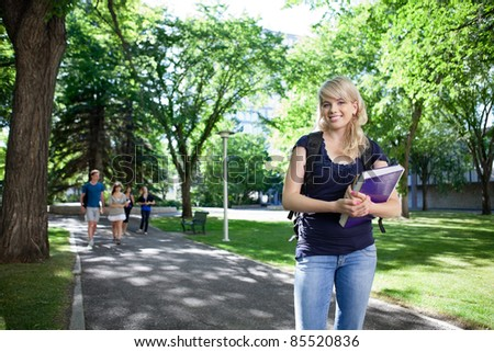 Portrait of smiling college girl holding book while her friends walking in background - stock photo
