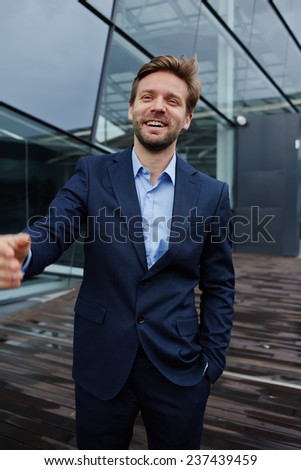 Portrait of smiling confident businessman, happy businessman or manager standing against skyscraper office building, wealthy successful man in suit smiling, portrait handsome man with great smile
