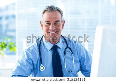 Portrait of smiling confident doctor sitting in hospital