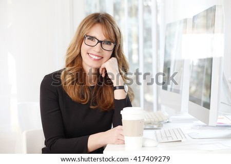 Portrait of smiling confident professional woman drinking coffee and relaxing at office.