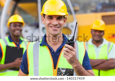 portrait of smiling contractor with walkie-talkie - stock photo