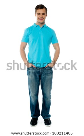 Portrait of smiling cool young guy standing with arms in his pocket - stock photo