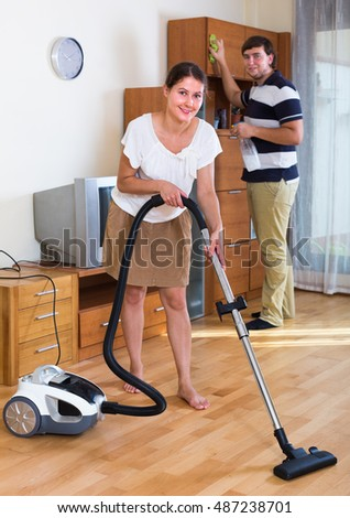 Portrait of smiling couple cleaning in the living room together