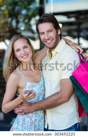 Portrait of smiling couple embracing and holding smartphone at shopping mall