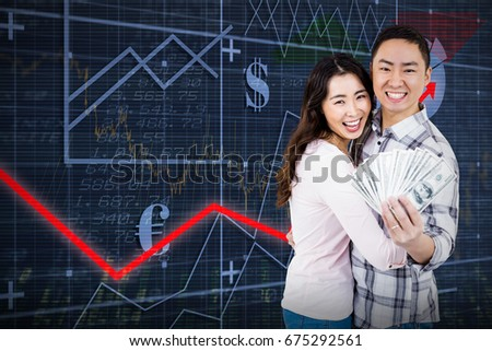 Portrait of smiling couple holding money  against red arrow