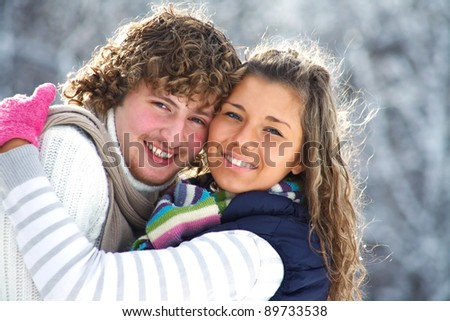 Portrait of smiling couple in winter park - stock photo