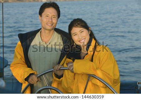 Portrait of smiling couple in yellow anoraks at steering wheel of sailboat against the sea - stock photo