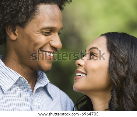 Portrait of smiling couple looking into eachother's eyes.