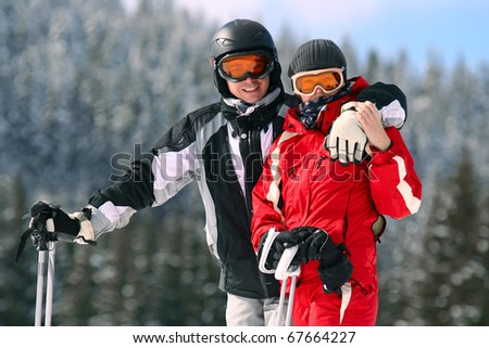 Portrait of smiling couple on skis in the mountains - stock photo