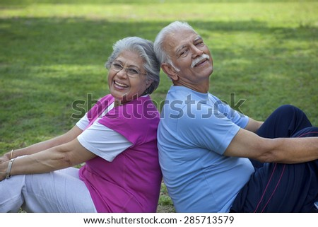Portrait of smiling couple sitting back to back in a park