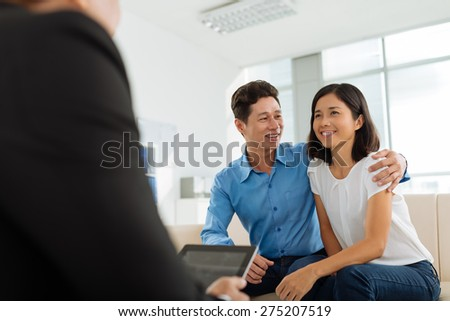 Portrait of smiling couple talking to estate agent - stock photo