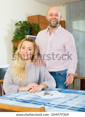 Portrait of smiling couple with contract for buying apartment and keys. Focus on woman  - stock photo