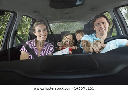Portrait of smiling couple with two cheerful children in car - stock photo