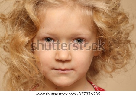portrait of smiling curly little girl indoors