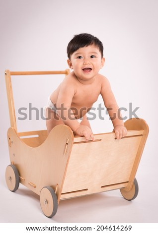 Portrait of smiling cute baby boy standing in a wooden cart. Isolated on white - stock photo