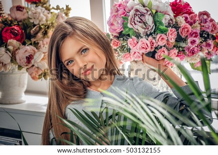Portrait of smiling cute blonde teenage girl with the colorful flower bouquet.