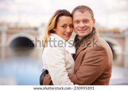 Portrait of smiling dates embracing and looking at camera in urban environment - stock photo