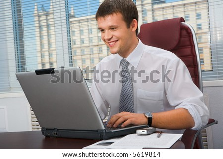 Portrait of smiling director sitting at the table and typing on his laptop