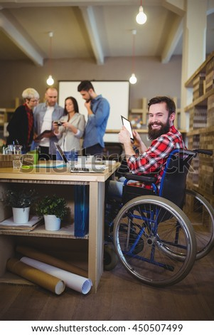 Portrait of smiling disabled businessman using digital tablet at desk in creative office - stock photo